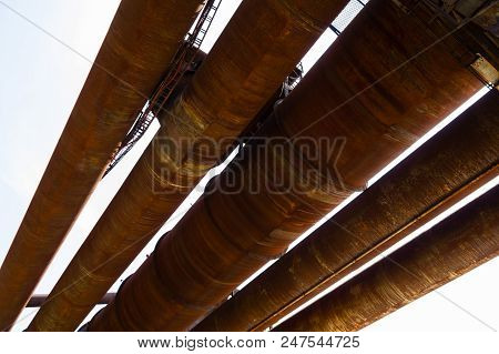 A Set Of Massive Rusty Old Pipelines In An Industrial Area