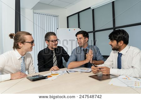 Young Ambitious Businessman Talking To Coworkers At Meeting. Positive Business Executives Discussing