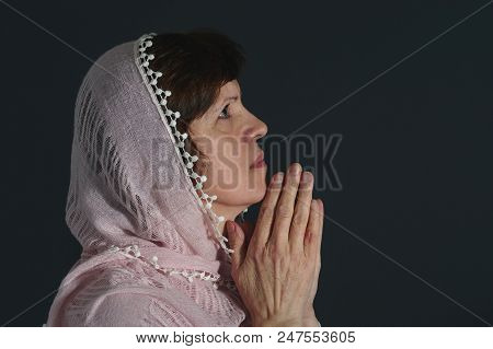 Portrait Of Beautiful Praying Caucasian Woman Wearing Cream-colored Shawl Against Dark Background.