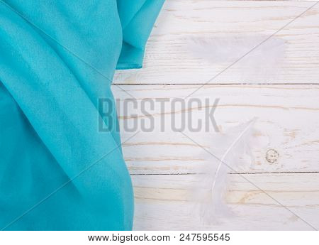 Folded Fabric Of Turquoise Color And Two White Feathers On A White Wooden Background (tranquility Co