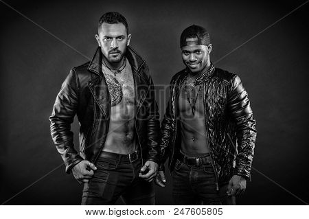 Machos with muscular torsos look attractive in leather jackets, dark background. Masculinity and brutality concept. Men on confident faces with bristle. Men with sexy muscular torsos look brutally. poster