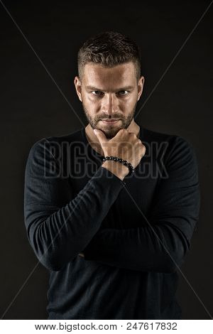 Man With Evil Look Isolated On Dark Background. Macho Touching His Beard. Man In Black Jumper Wearin