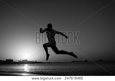 Running Man. Sport And Run Concept. Silhouette Of Running Man On Sunset Fiery Sky Background In Sea,
