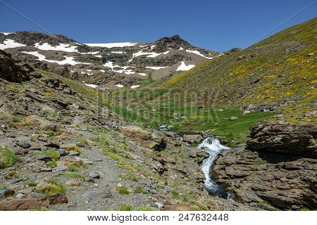 Rear View Panorama Of Hikers Ascending Mountain With Snowfields
