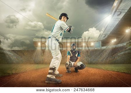 Baseball players in dynamic action under sunset sky on the stadium.