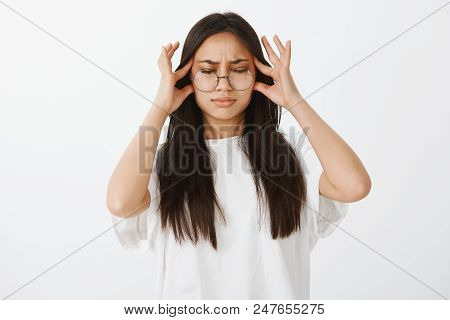 Trying Pull Emotions Together. Studio Shot Of Displeased Unhappy European Woman In Glasses, Closing