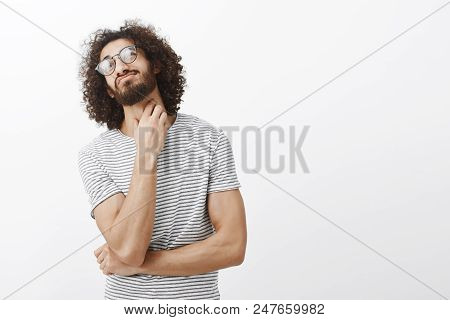 Studio Shot Of Unsure Confused Attractive Hispanic Guy With Stylish Curly Haircut In Glasses, Tiltin