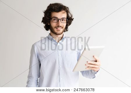 Portrait Of Happy Young Man Wearing Glasses Using Touchpad. Young Caucasian Businessman With Digital