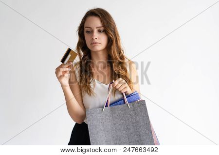 Portrait Of Sad Woman With Shopping Bags Looking At Credit Card. Young Caucasian Shopper Wearing Whi