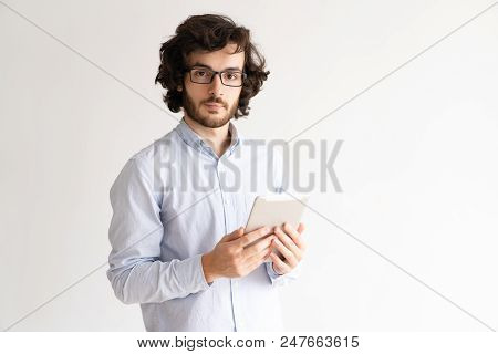 Portrait Of Serious Businessman In Glasses With Digital Tablet. Confident Young Caucasian Man Using