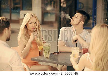 Friends In The Bar. Man Vapor Hookah Pipe In Shisha Bar Lounge. Women Twins And Men Friends Relax In
