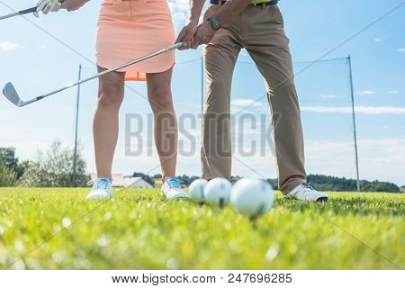 Low section of man and woman holding iron clubs, while practicing together the correct grip and move for playing golf on the green grass of a professional ground poster