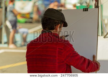Man Draws The Portrait On White Paper At The Street.