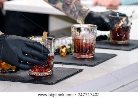 Man Preparing Three Classic Alcoholic Godfather Cocktails, Shallow Dof