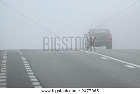 Car Disappearing Through Fog