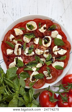 Caprese salad made with tomatoes, bocconcini, basil and balsamic.  Overhead view.