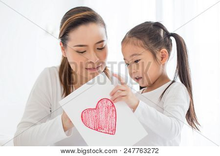 Attractive Little Girl Writing Heart On Paper. Mom Teaching Her At Home. Children Lifestyle, Educati