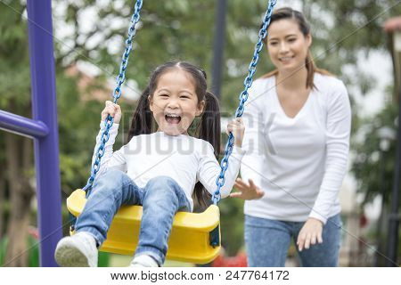 Mom Is Playing With Her Little Daughter On A Terrace With Swings. Family Lifestyle Concept. Beautifu