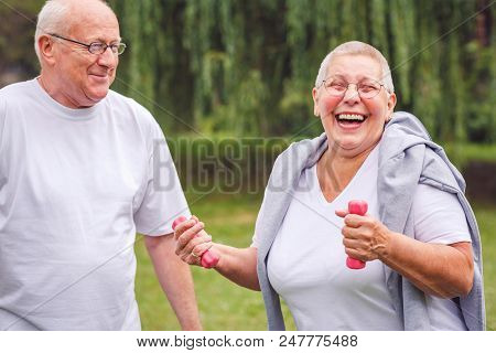 Happy Senior Couple Exercise In Park Together