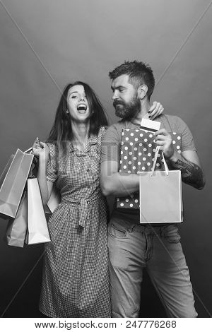Shopping And Fashion Concept. Guy With Beard And Pretty Lady With Happy Face Do Shopping. Bearded Ma