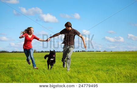 Jonge hond op een groene weide met en gelukkige familie