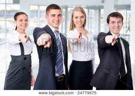Happy business people of executives all pointing at you