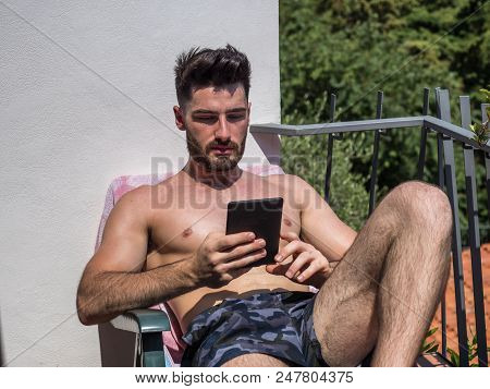 Shirtless Young Man Drying Off In Hot Sun Reading An Ebook With Electronic Reader, Muscular Man Wear