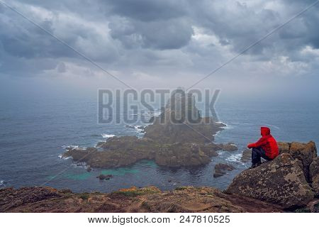 Lonely Tourist Dressed In Waterproof Jacket Sitting On The Top Of A Cliff And Admiring The Rocky For