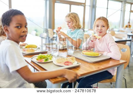 Group of kids in the canteen of the elementary school having lunch