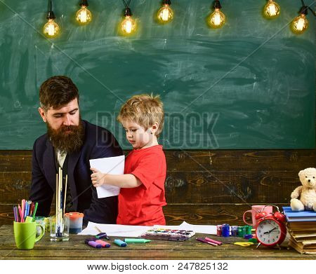 Informal Education Concept. Art Lesson In The Kindergarten. Cute Boy Showing Teacher His Drawing.