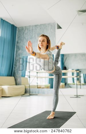 Full Length Portrait Of Young Fit Woman Doing A Yoga Pose Standing With One Leg Raised Up. Utthita H