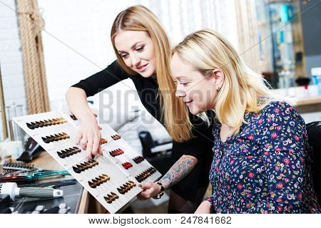 Stylist helps female client to choose hair dye color with hair swatches chart poster