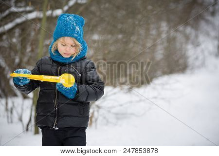 Portrait Of Adorable Little Kid Boy With Long Blond Hair Playing With Snowballs Outdoors..child With