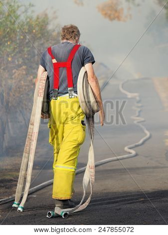 Melbourne, Australia - April 13, 2018: Fire Fighter With Rolls Of Fire Hose At A Bush Fire In An Sub