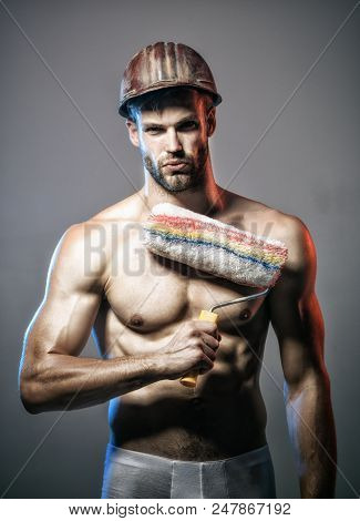 Sexy muscular worker, painter, decorator, contractor, builder with beard and mustache in helmet with paint roller. Renovation and decoration concept - confident professional painter holds paint roller poster