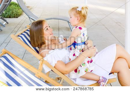 Happy Mother And Daughter Sitting, Relaxing In The Deckchair In The City Park Recreation Area And Ha