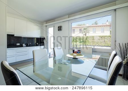 White kitchen with black marble and an elegant glass table and leather chairs. Nobody inside