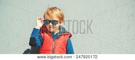 Stylish Kid In Trendy Sunglasses. Kids Fashion. Cute Little Blondy Boy In Red Jacket Standing Over G