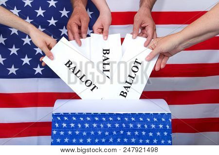 Hands Placing Ballots In A Voting Box, American Flag In Background. Anyone Over The Age Of 18 On Ele