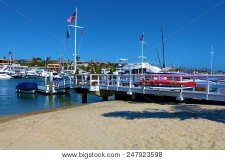 July 2, 2018 In Balboa Island, Ca:  Sandy Beach Cove Beside A Public Pier Surrounded By Docked Yacht