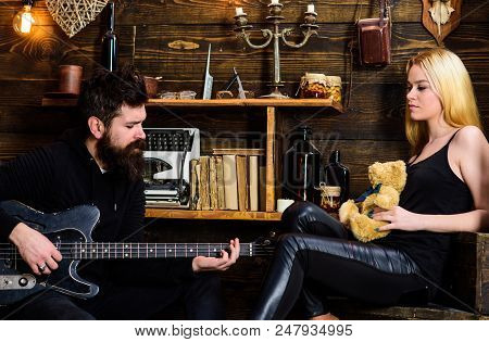 Romantic Date Concept. Man Play Guitar While Lady Holds Teddy Bear In Hands. Couple Spend Romantic E
