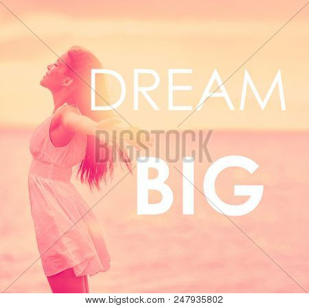 DREAM BIG inspirational message written on motivational picture of carefree girl happy with arms open in freedom at beach sunset. Life happiness motivation quote for dreaming big in your life.