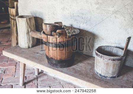 Old wooden barrel and scoop. Wooden barrel, trough, scoop in old country house. poster