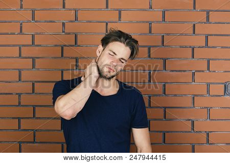 Man With Fair Hair On Red Brick Wall Background. Illnesses And Health Care Concept. Macho With Suffe