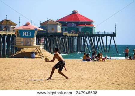 July2, 2018 In Huntington Beach, Ca:  Man Serving A Volleyball With The Huntington Beach, Ca Pier Be
