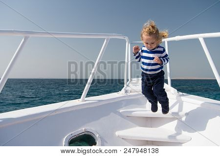 Freedom And Joy. Adventure Boy Sailor Travelling Sea. Child Cute Sailor Carefree Jump Yacht Bow. Boy