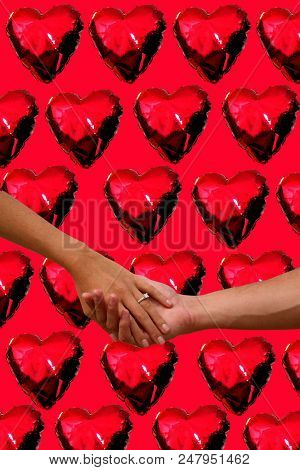 Engagement love. A couple holds hands with an engagement ring in front of a Heart Background. Love is in the air.