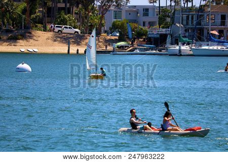 July 2, 2018 In Newport Beach, Ca:  People Kayaking And Sailing In A Small Sail Boat Called A Dinghy