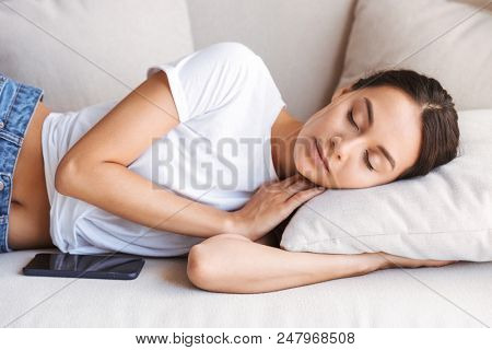 Pretty young asian woman sleeping with mobile phone on couch at home