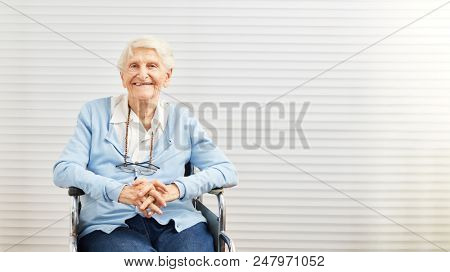 Smiling old woman sits in wheelchair in retirement home
